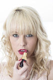 Young Woman Applying Red Lipstick Stock Image