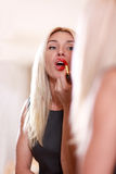 Young woman applying red lipstick Royalty Free Stock Photography