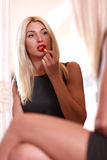 Young woman applying red lipstick Royalty Free Stock Images