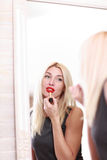 Young woman applying red lipstick Stock Photo