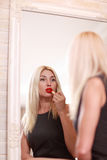 Young woman applying red lipstick Stock Photos