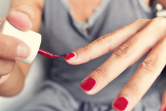 Young woman applying red nail polish to her fingernails Stock Photography