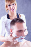 Young woman applying shaving cream on male face stock photos