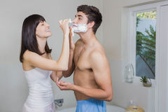 Young woman applying shaving cream on young mans face Stock Photography