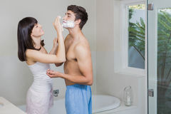 Young woman applying shaving cream on young mans face Stock Image