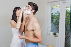 Young woman applying shaving cream on young mans face Stock Images