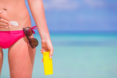 Young woman applying stomach with sunscreen on. Young woman apply cream on her nose at beach Stock Image