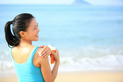Young woman applying sun block cream body Stock Photos