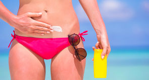 Young woman applying sun cream during beach Stock Photography