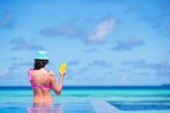 Young woman applying sun cream during beach. Young woman apply cream on her nose at beach Stock Photo