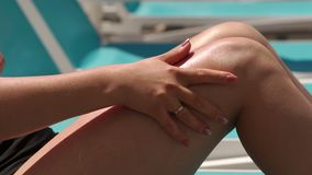 Young woman is applying sun cream on her smooth tanned legs by the pool.