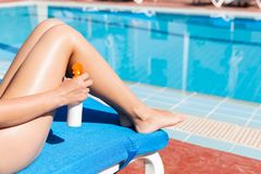 Young woman is applying sun cream on her smooth tanned legs by the pool. Sun Protection Factor in vacation, concept royalty free stock photography