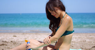Young woman applying sun cream to her legs Stock Photo