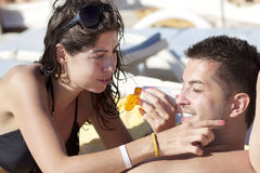 Young  woman applying sun-protection cream on her boyfriend. Happy couple on the beach.summer time Royalty Free Stock Photography