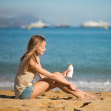 Young woman applying sunscreen on her legs Royalty Free Stock Photos
