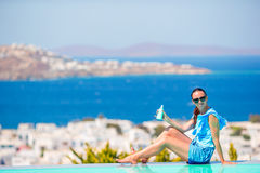 Young woman applying sunscreen on her legs, sitting on the edge of pool background old town Mykonos in Europe Stock Images