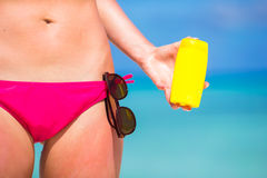 Young woman applying with sunscreen on white beach. Young woman apply cream on her nose at beach Stock Photography