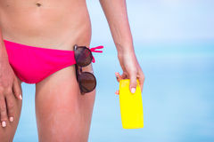 Young woman applying with sunscreen on white beach. Young woman apply cream on her nose at beach Royalty Free Stock Photo