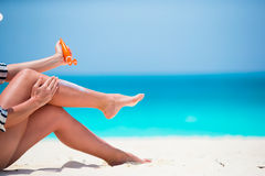 Young woman applying with sunscreen on white beach Stock Photos