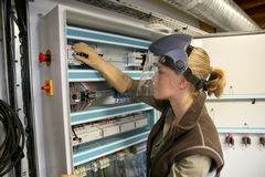 Young woman apprentice checking electronical system. Young woman checking electrical system of heating room Royalty Free Stock Photos