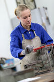 Young woman apprentice learning ironworks Stock Image