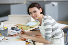 Young woman apprentice painter sitting at working table Royalty Free Stock Image