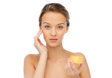 Young woman appying cream to her face Stock Photo