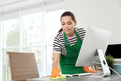 Young woman in apron and gloves cleaning office. Young woman in apron and gloves cleaning table at office royalty free stock image
