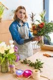 Young woman in apron holding beautiful bouquet and looking at camera. In flower shop stock photos