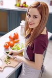 Young woman in apron making a salad. Enjoy cooking. The top view of a pretty cheerful young woman in an apron smiling at the camera while cutting cucumbers and Royalty Free Stock Photo