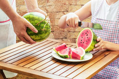 Young woman in apron slicing fresh ripe juicy red watermelon Stock Photos