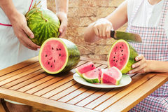 Young woman in apron slicing fresh ripe juicy watermelon Stock Photo