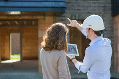 Young woman and architect on construction site. View of a Young women and architect on construction site Royalty Free Stock Images