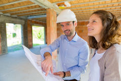 Young woman and architect on construction site royalty free stock image