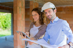 Young woman and architect on construction site Stock Images
