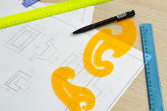 Young woman - architect draws a plan, graphic, design, geometric shapes by pencil on large sheet of paper at office desk. crop ima Royalty Free Stock Images