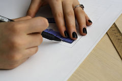 Young woman - architect draws a plan, graphic, design, geometric shapes by pencil on large sheet of paper at office desk. crop ima Royalty Free Stock Photography