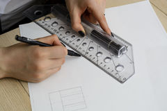 Young woman - architect draws a plan, graphic, design, geometric shapes by pencil on large sheet of paper at office desk. crop ima Stock Image