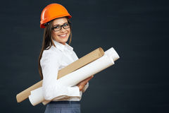 Young woman architect holding blueprint. Smiling woman real estate manager. Black background Royalty Free Stock Photo