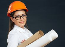 Young woman architect holding blueprint. Smiling woman real estate manager. Black background Royalty Free Stock Photography