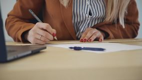 Young woman architect working with new blueprint sitting at table in office room. stock footage