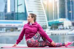 Young woman in Ardha Matsyendrasana pose against city and river Stock Photos
