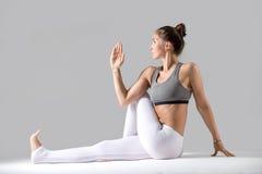 Young woman in Ardha Matsyendrasana pose, grey studio background Stock Photos