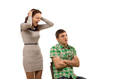Young woman arguing with her boyfriend. Young women arguing with her boyfriend yelling at him as he sits in a chair with his arms folded staring upwards as he Royalty Free Stock Photos