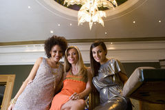 Young woman arm in arm with friends, smiling, portrait, low angle view Stock Images