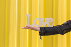Young woman arm holding  LOVE Word over yellow background. Casua Stock Photos