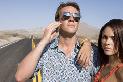 Young woman with arm on man in sunglasses using mobile phone on open road, portrait Stock Images