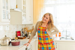 Young woman with arms crossed standing against kitchen interior Stock Photography
