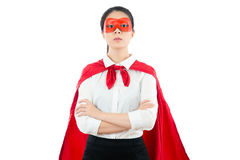 Young woman arms crossed wearing shirt. Acting superhero with red goggles and cape standing on copyspace area seriously looking closeup isolated on white wall Stock Image