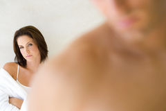 Young woman with arms folded, man in foreground (differential focus) Royalty Free Stock Photography